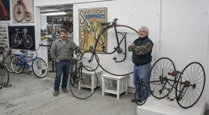 (L) Seth Fallon (R) Mike Fallon with Early poster Amsterdam Simplex, C. 1888 Singer Extraordinary 48 inch high wheel and C. 1886-1887 Gormully & Jeffery Ideal two track tricycle