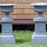 Pair of early cast iron three part urns
